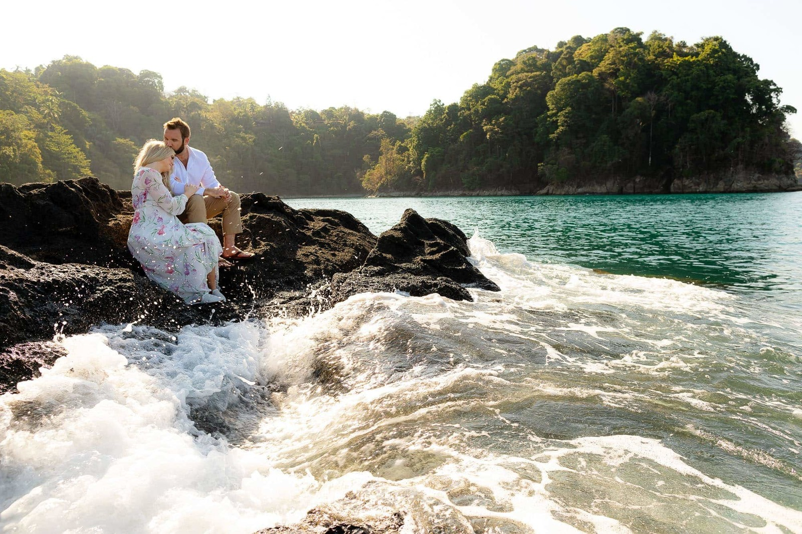 bride and groom on rocks by waves