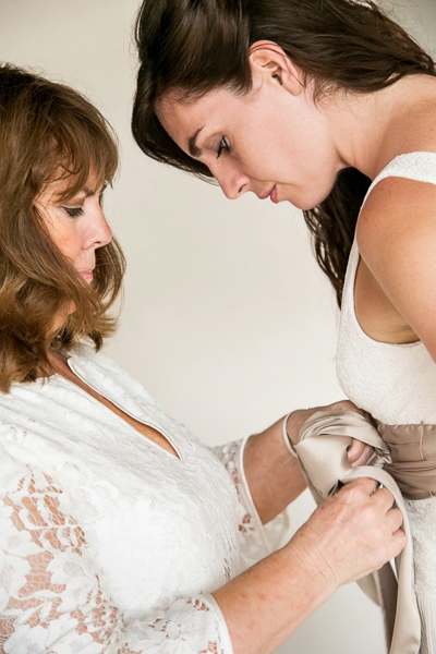 Photo of mother and daughter putting on sash on wedding day.
