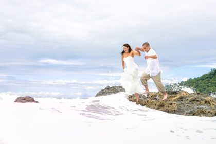 Bride and groom jumping from rock.