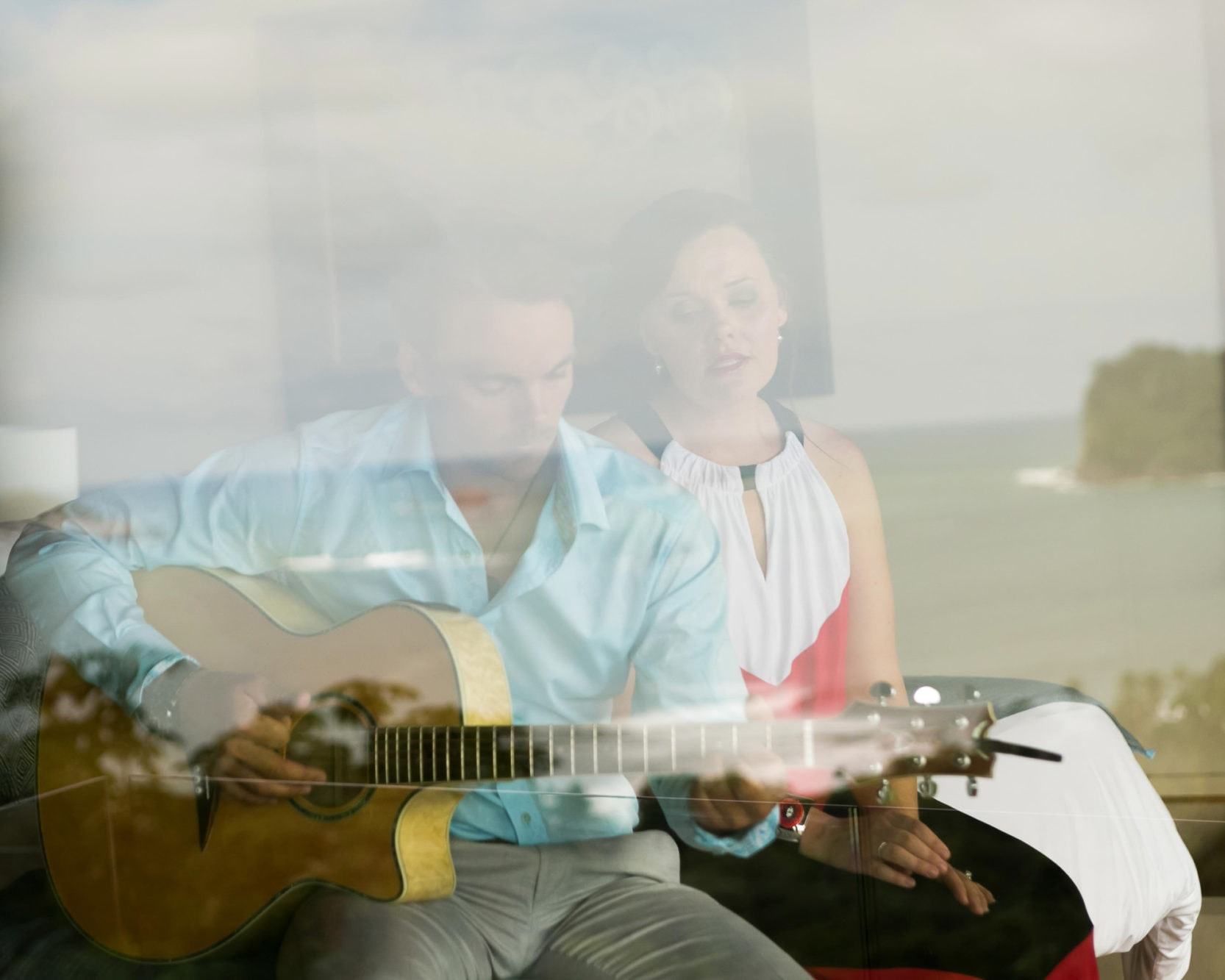 groom and sister playing guitar before wedding