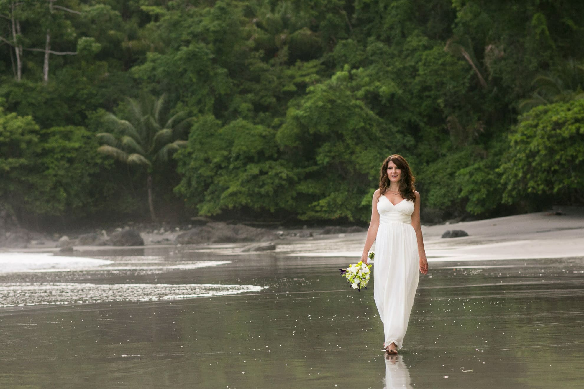 Bride walking on beach in Arenas del Mar.