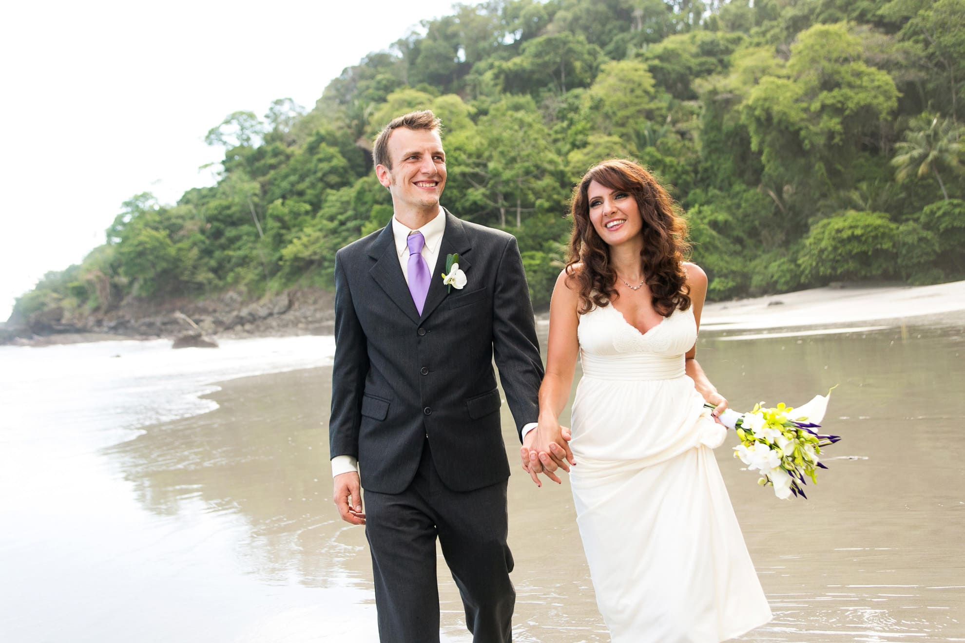 Bride and groom walking on beach after wedding ceremony.