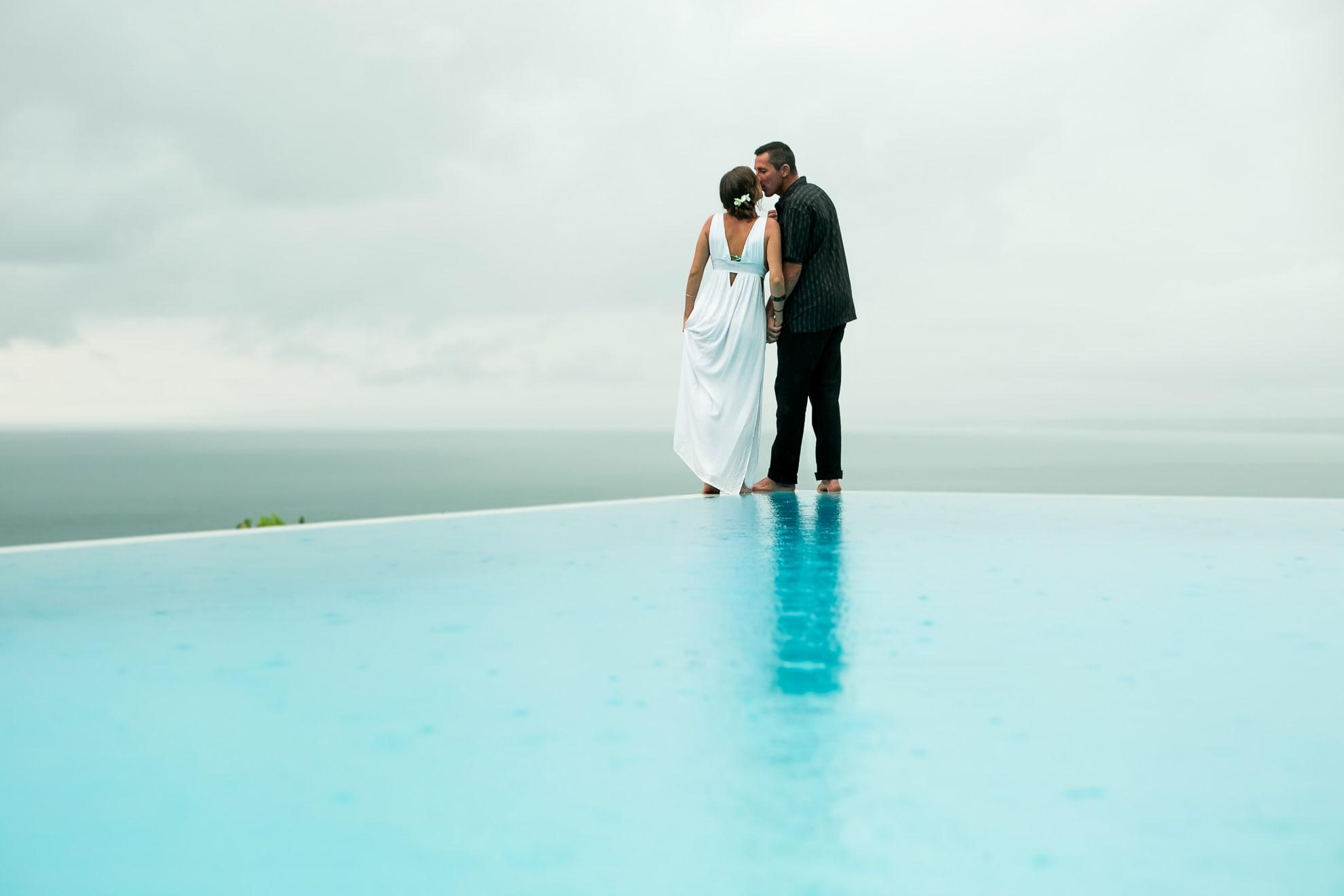 Bride and groom on infinity pool.
