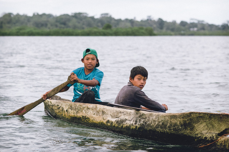 Kids fishing dug out canoe in Bocas del Toro