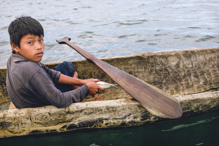 Boy fishing in canoe in Bocas del Toro