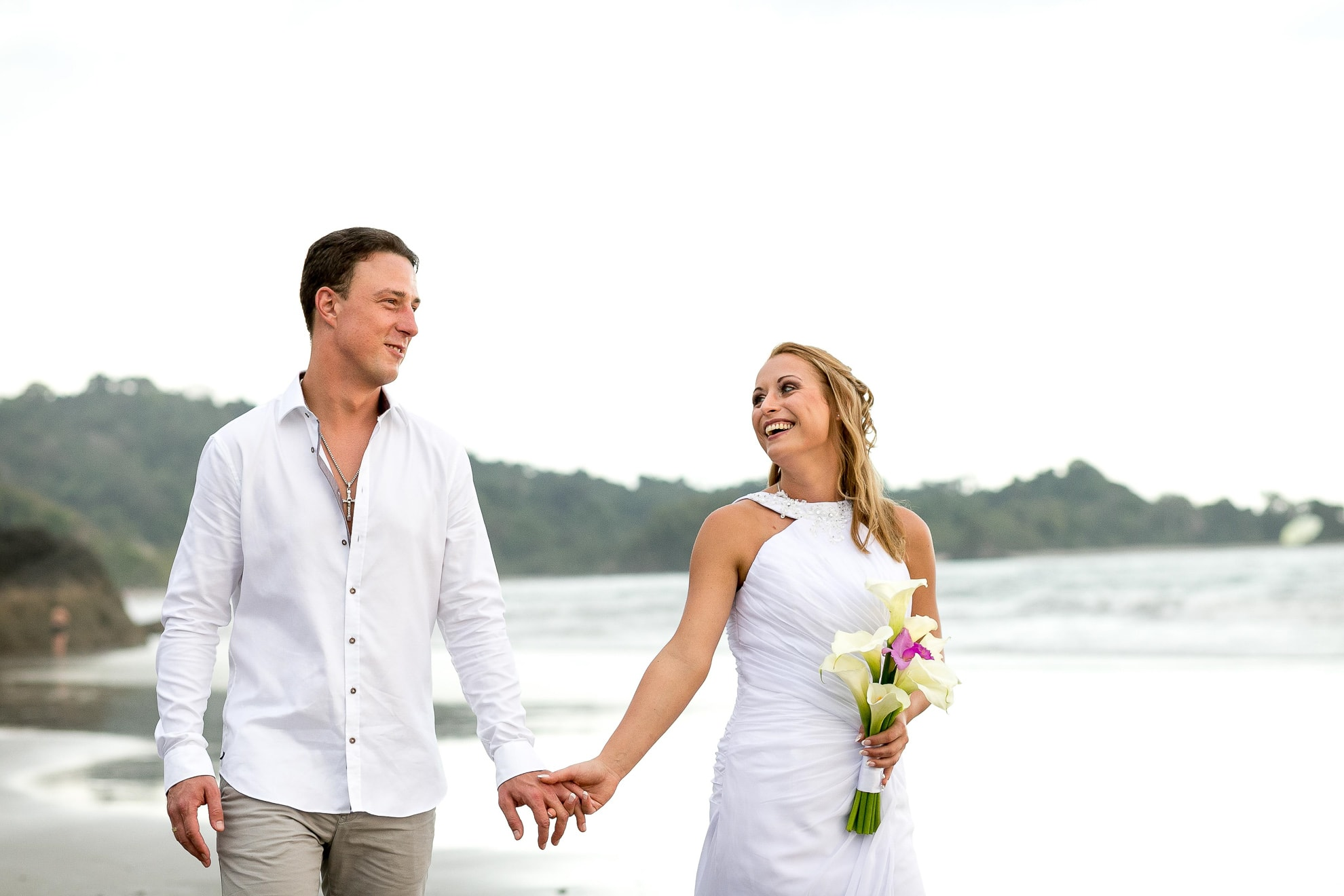 Bride and groom walking on beach in Costa Rica.