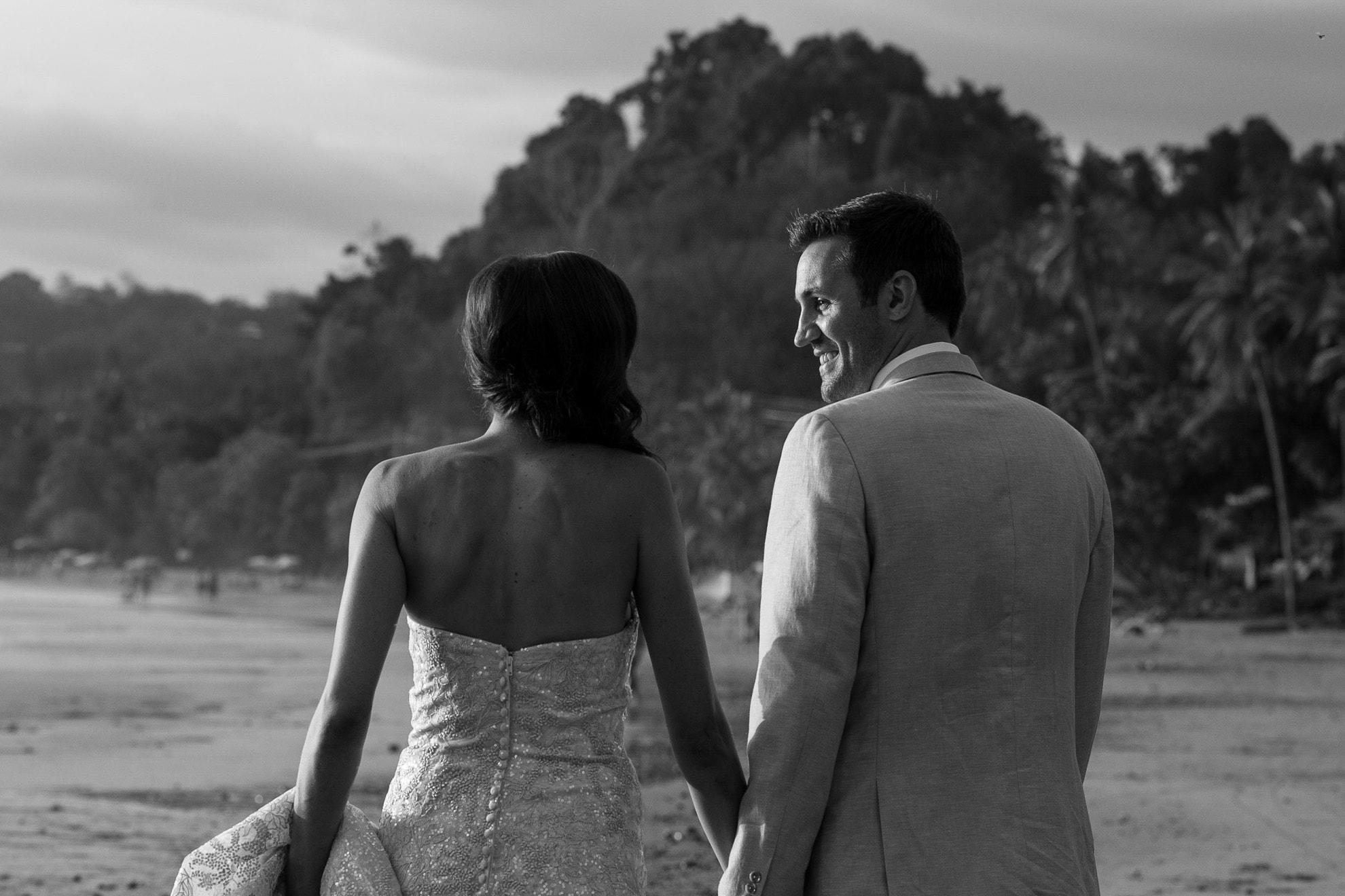Bride and groom walking at beach.