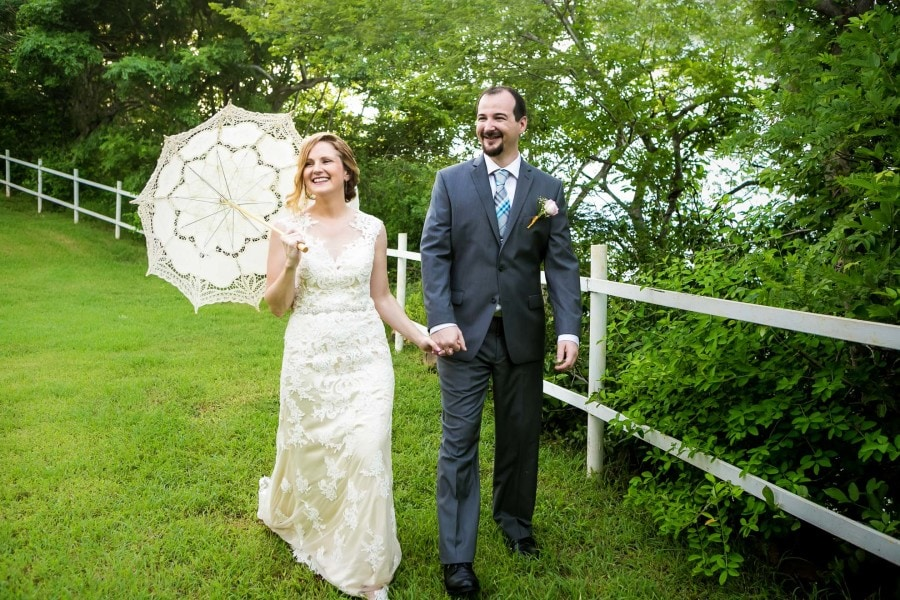 Bride and groom walk with parasol.