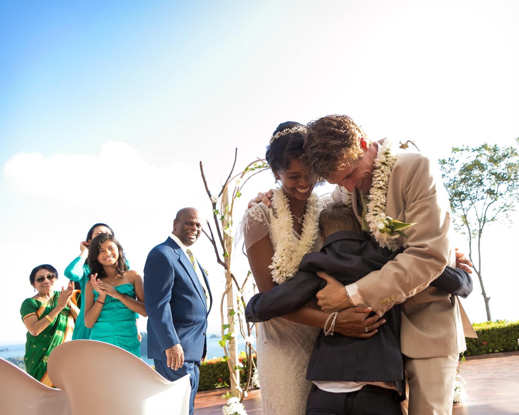 Wedding couple hugs son at wedding.