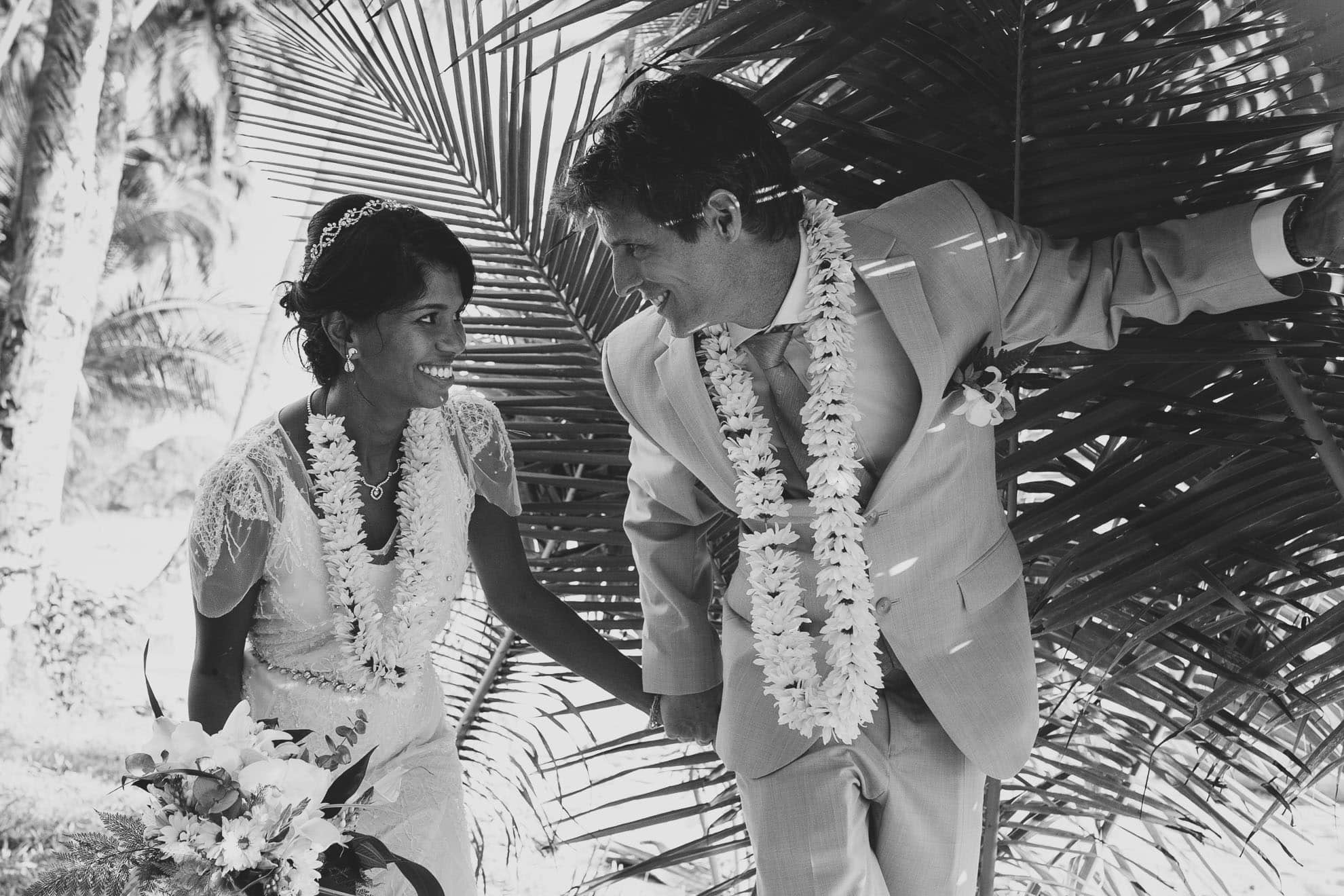 Bride and groom with palm leaves.