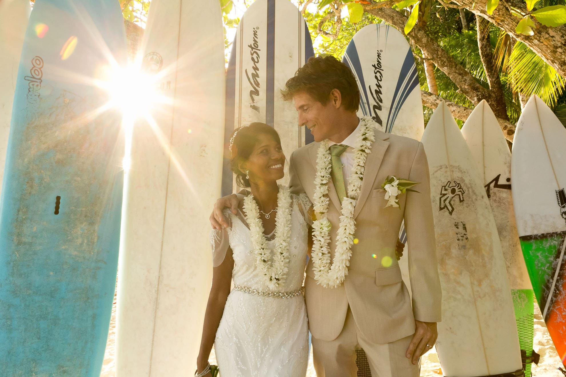 Bride and groom with surfboards.