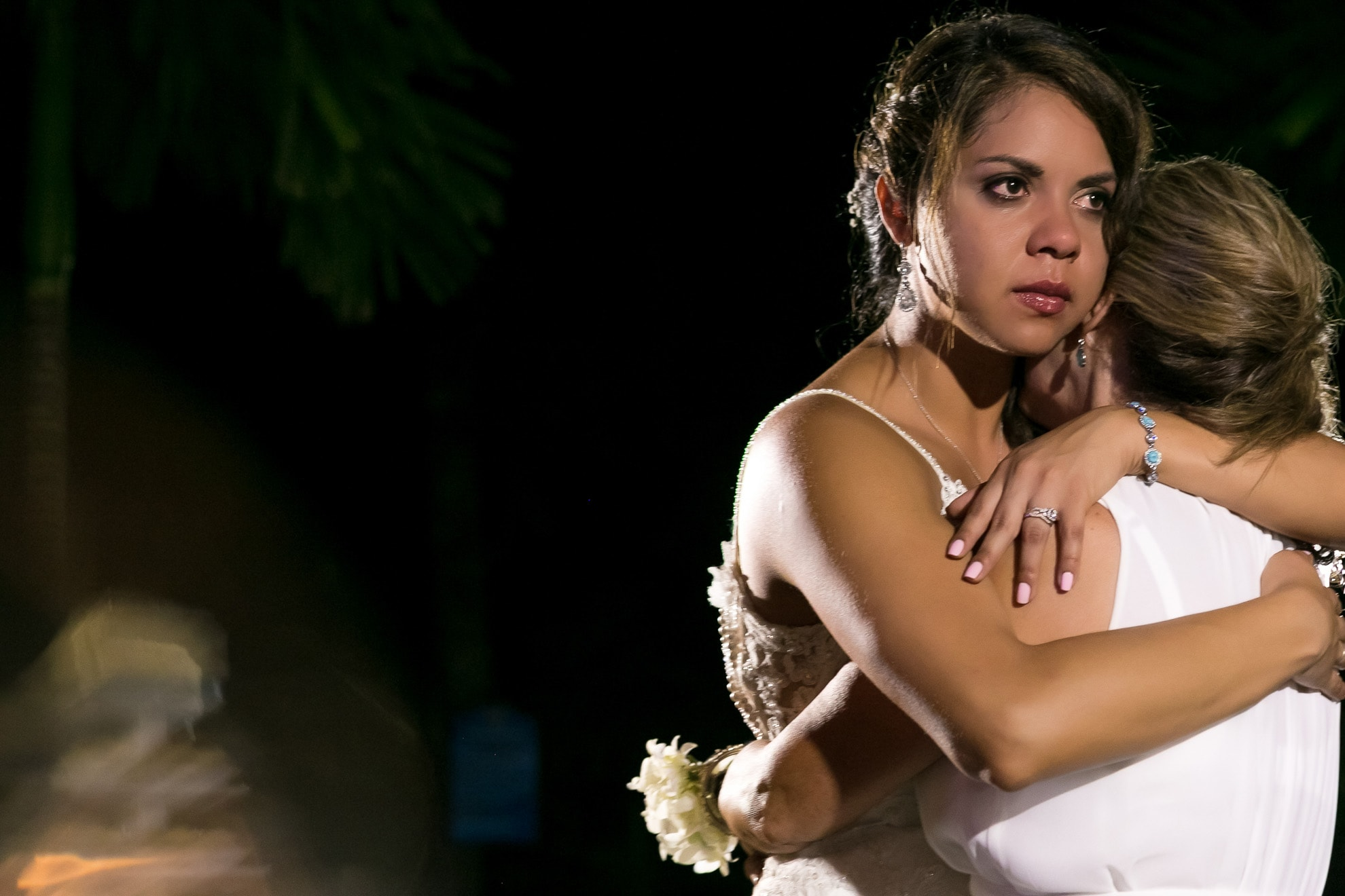 Bride hugs mother at wedding