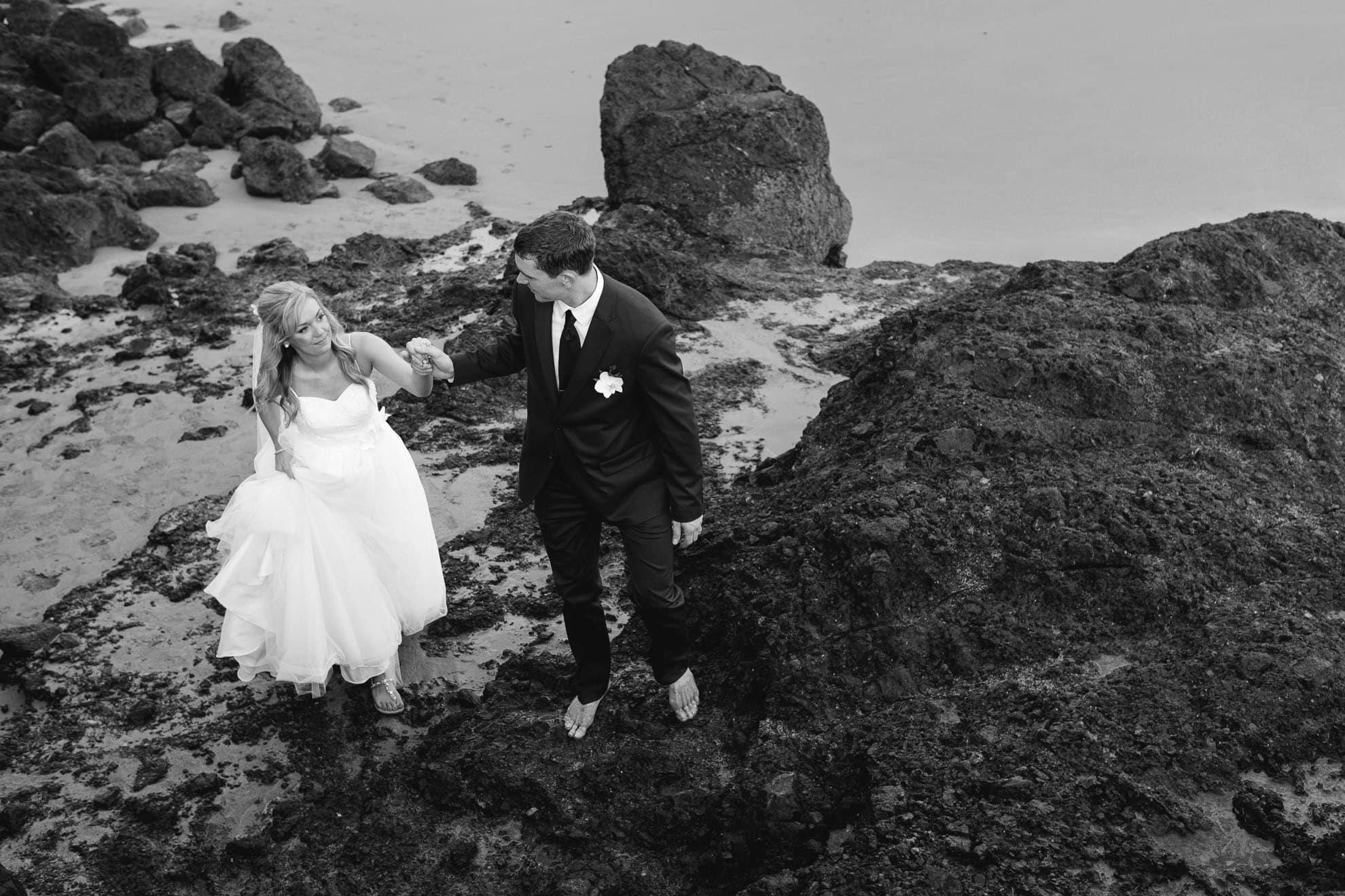 Bride and groom climbing rocks at wedding