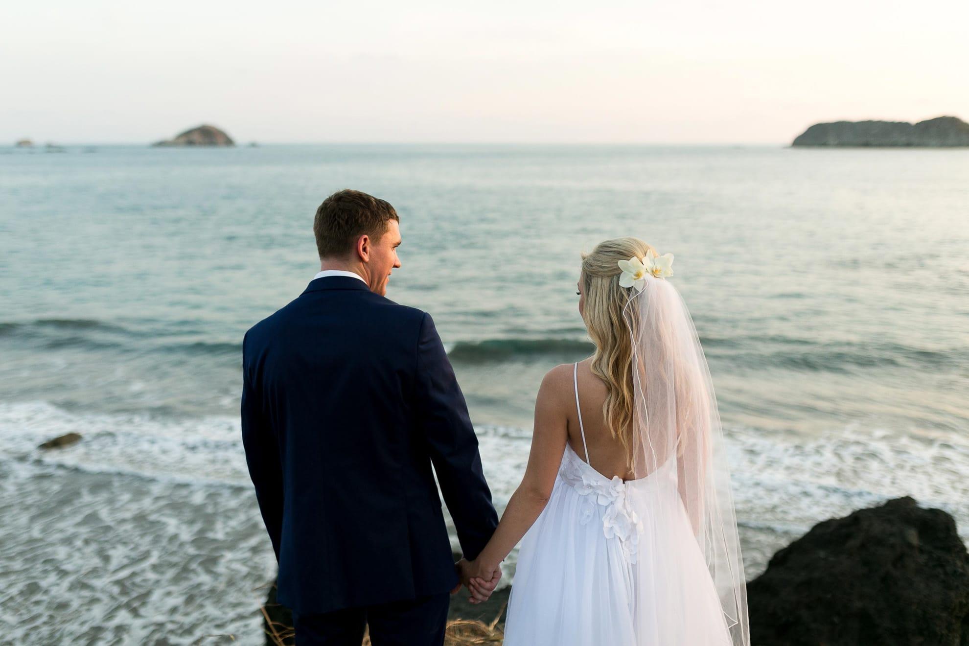 Bride and groom on high rocks at Playitas Manuel Antonio