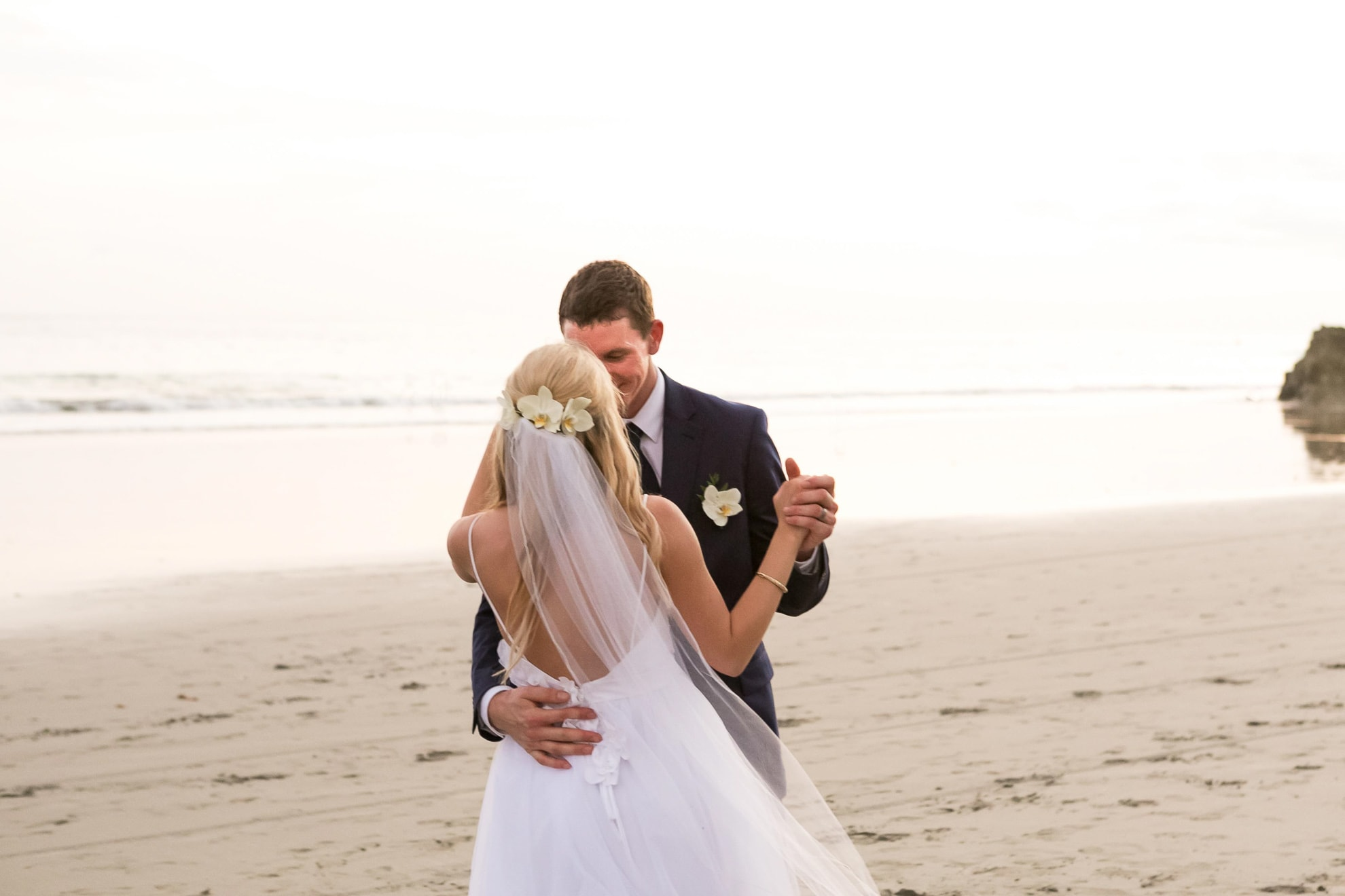 Bride and groom have first dance at beach.