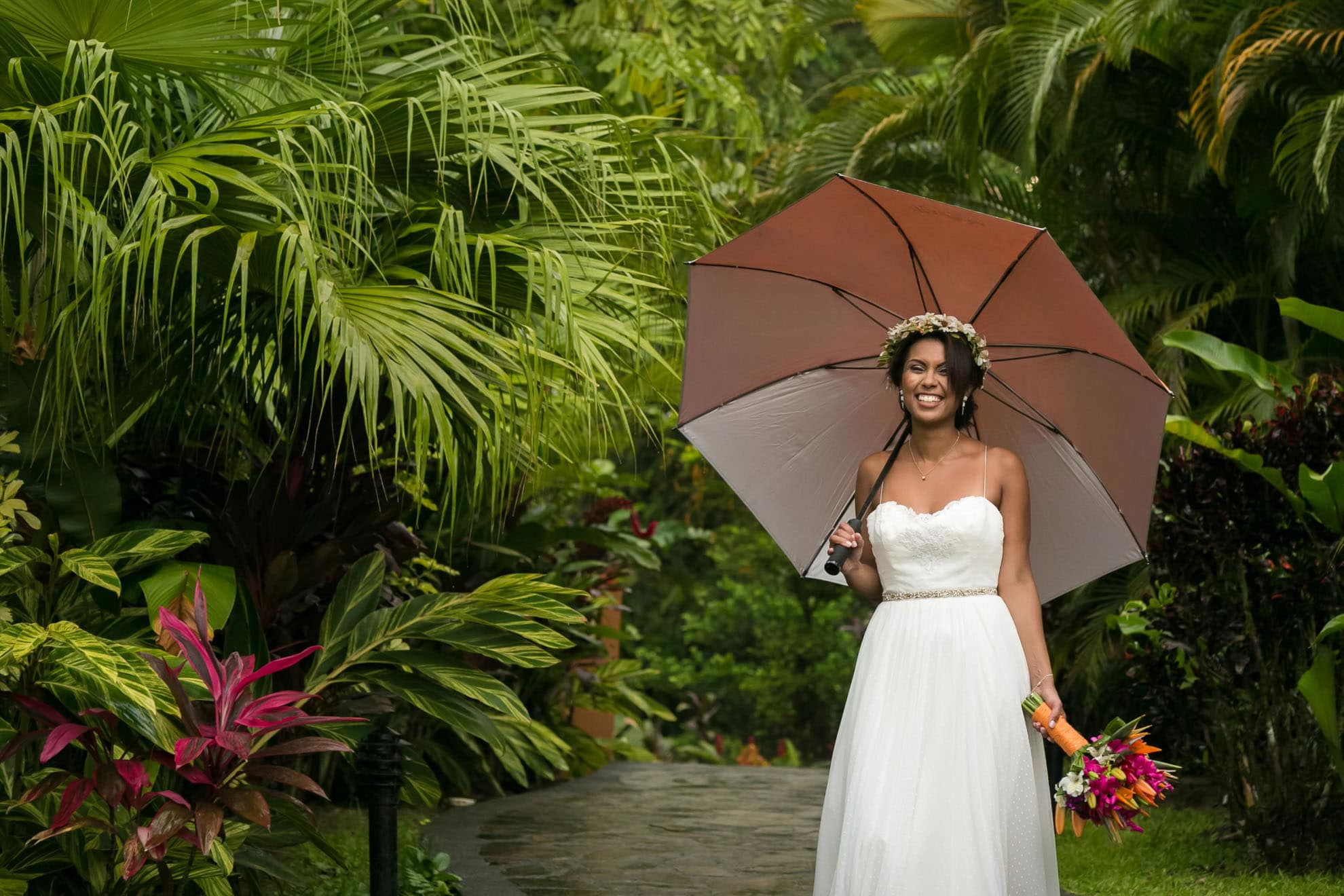 Bride with umbrella: the greenery is lush for a volcano wedding