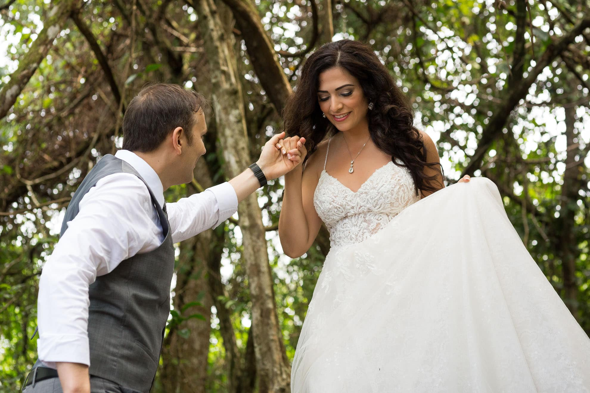 Groom helps bride walk down trail