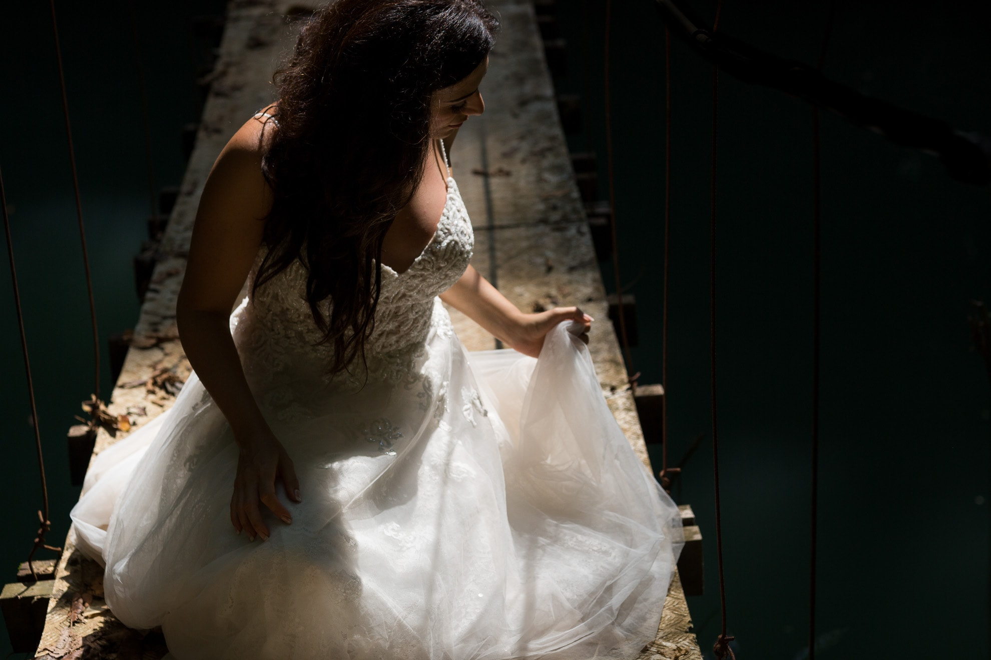 Bride on hanging bridge adjust dress