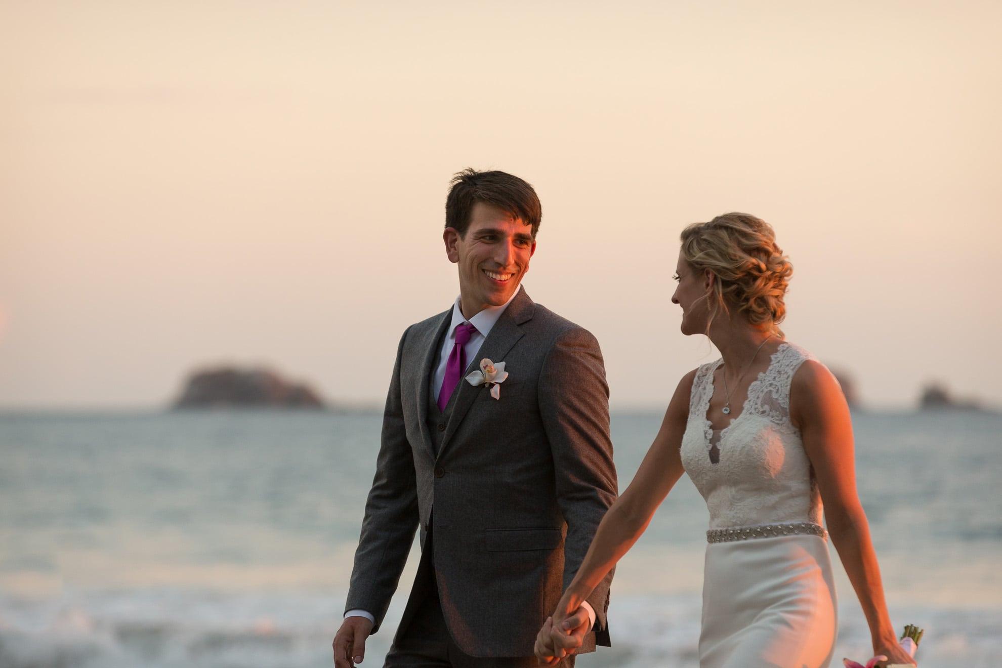bride and groom walking along manuel antonio beach