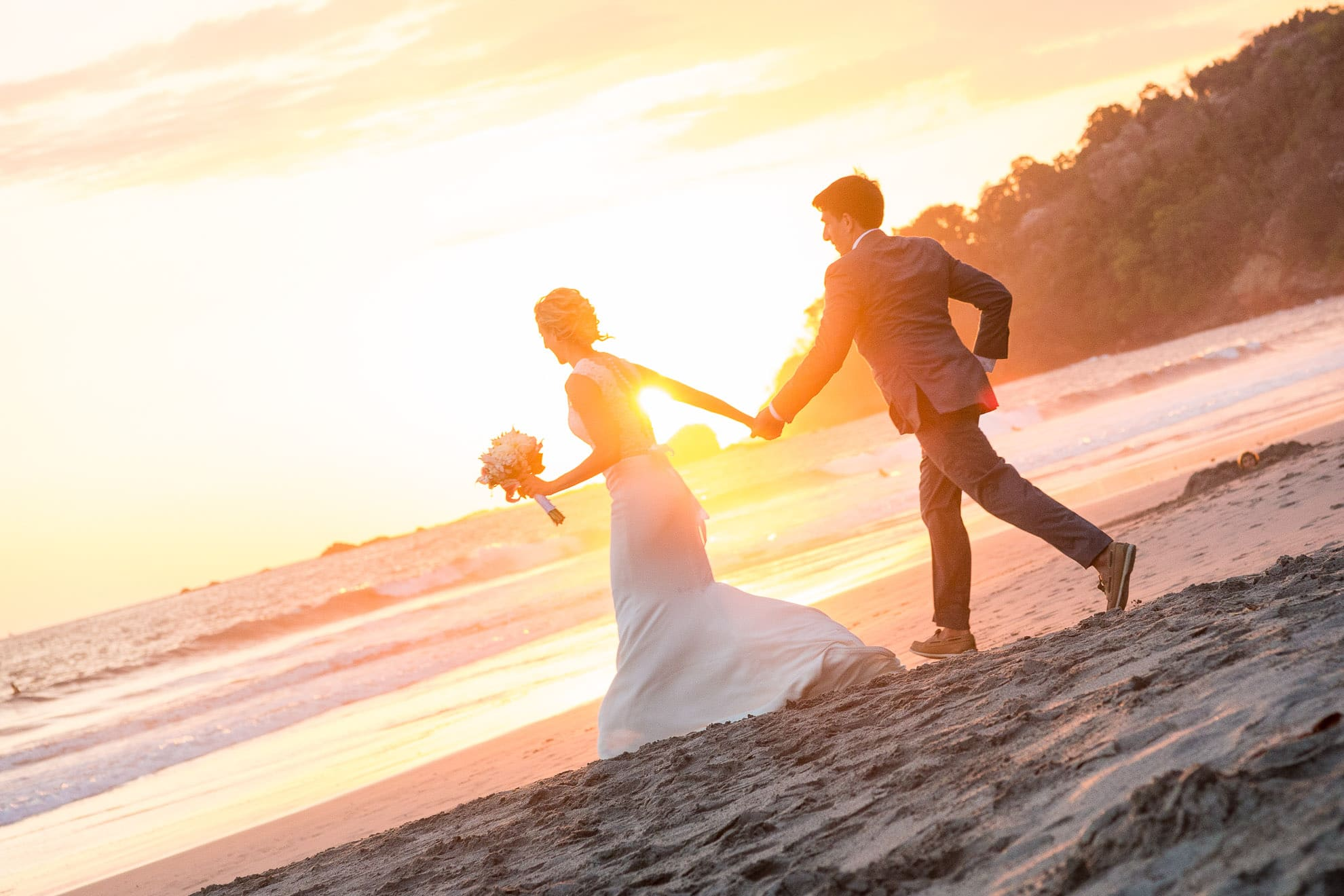 bride and groom running to catch the sunset