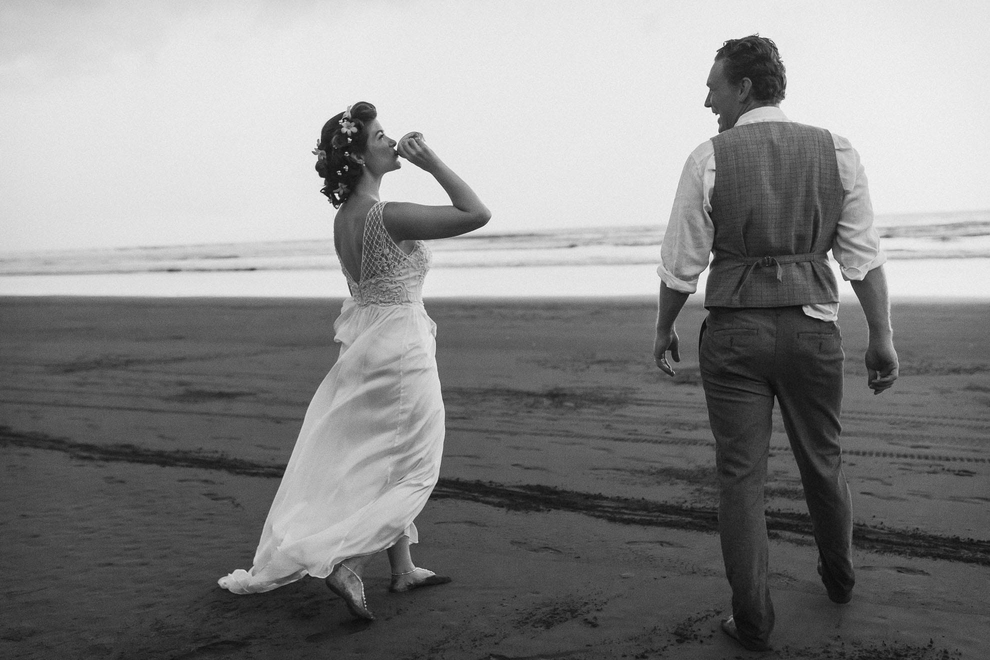 bride drinking from groom's flask on beach.