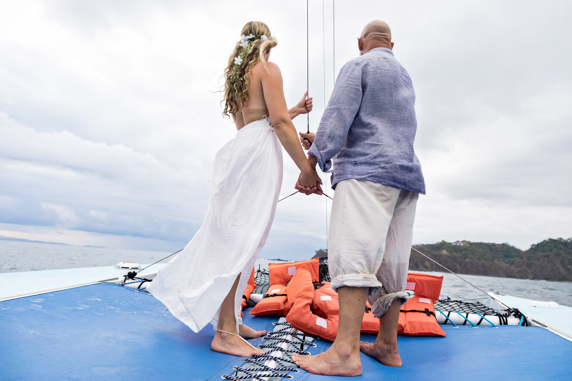 Destination wedding couple holding hands on the wedding boat and looking out to the horizon.