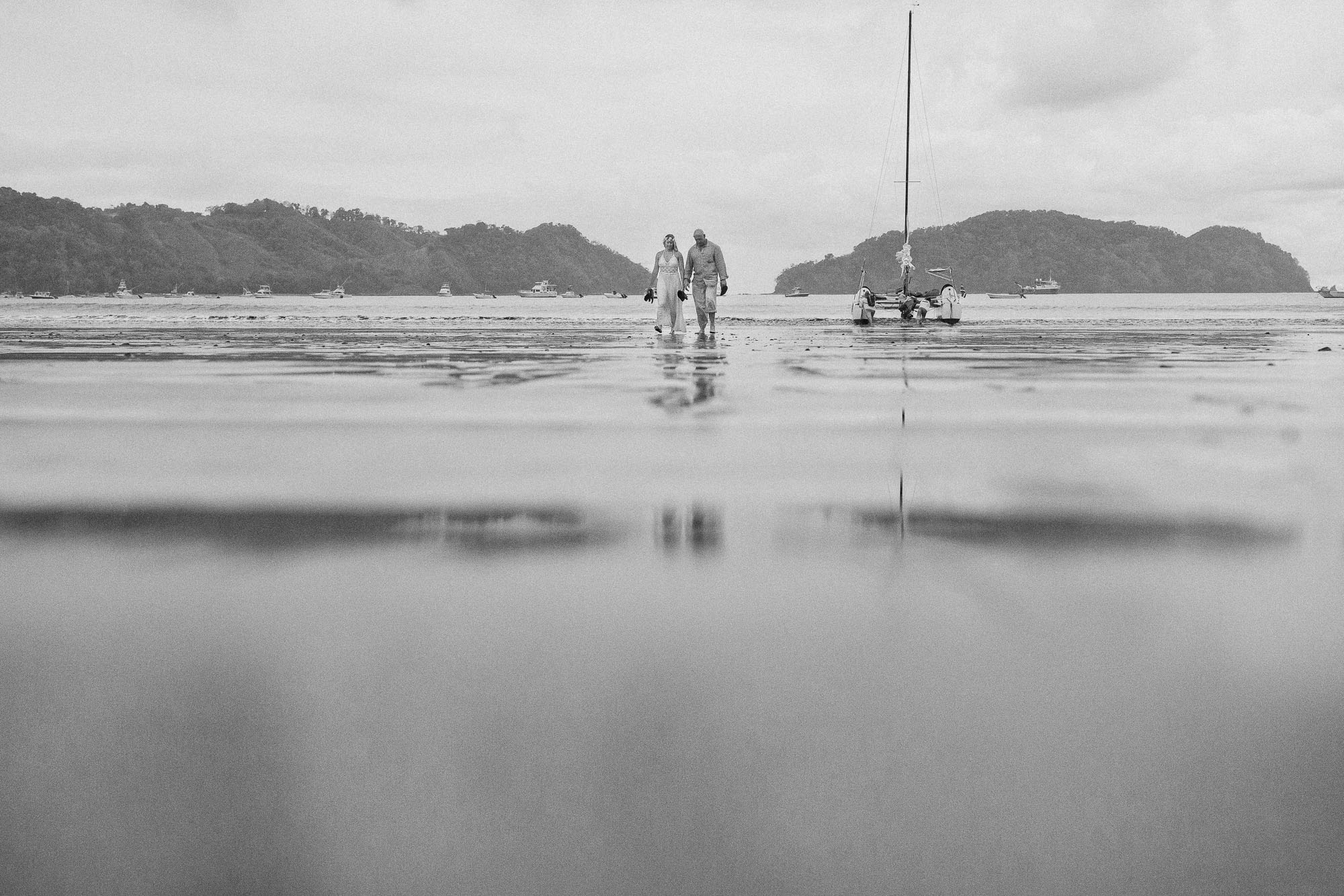 B&W photo of destination wedding couple with the wedding boat in the background.
