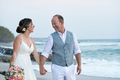 Bride and Groom walk hand in hand along the beach in Costa Rica