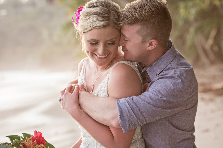 Bride and groom snuggle together for an intimate moment during their beach wedding