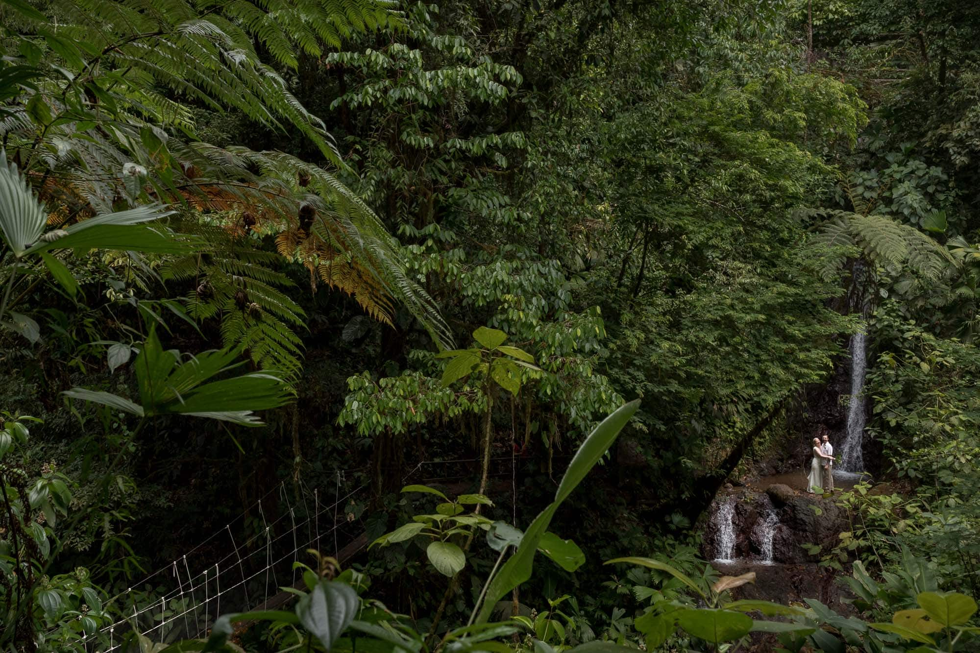 Bride and groom at base of waterfall in costa rican rainforest