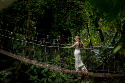 The bride strolling across a hanging bridge in the Costa Rican rainforest