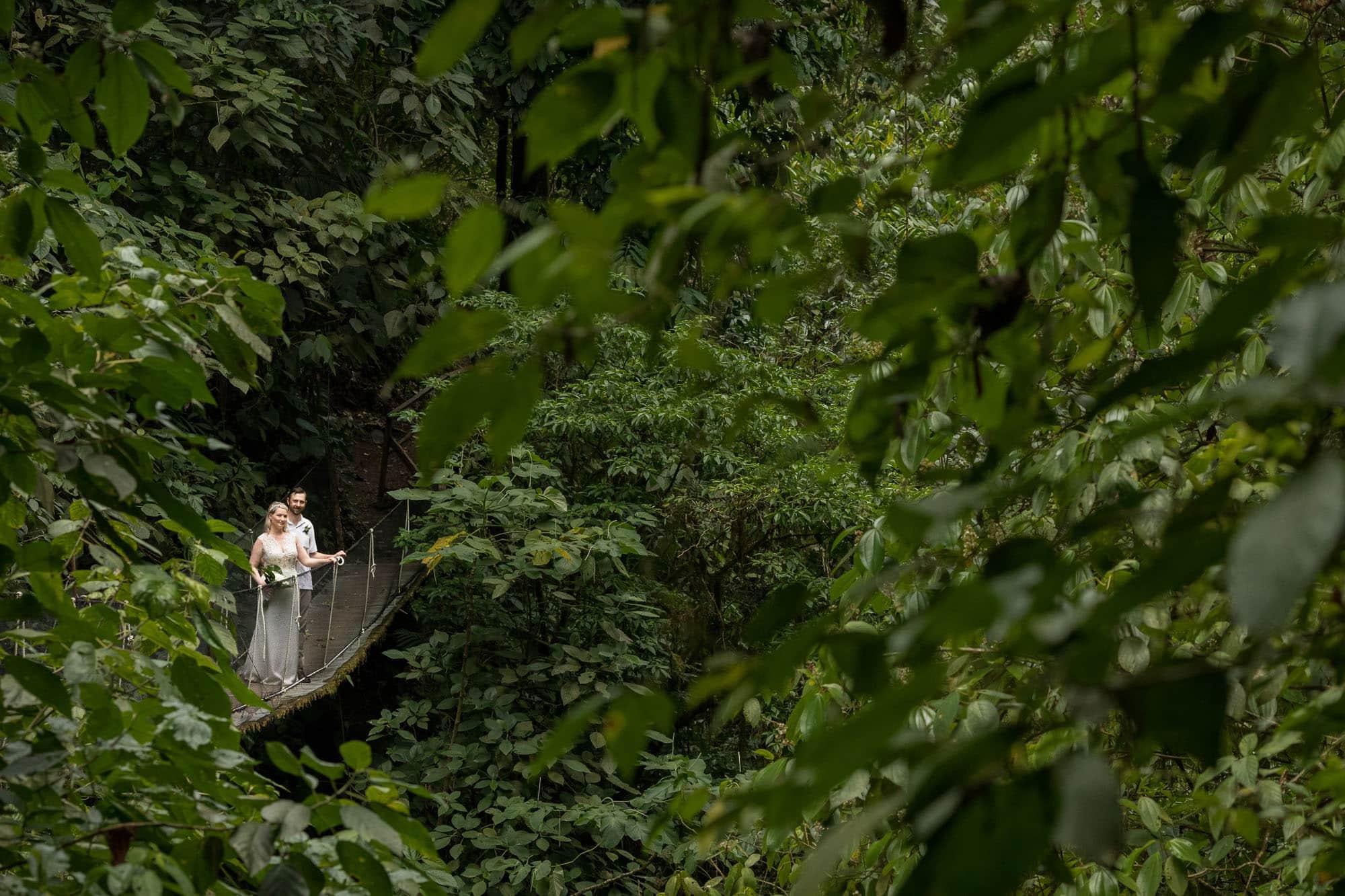 Bride and groom on suspension bridge in costa rican rainforest
