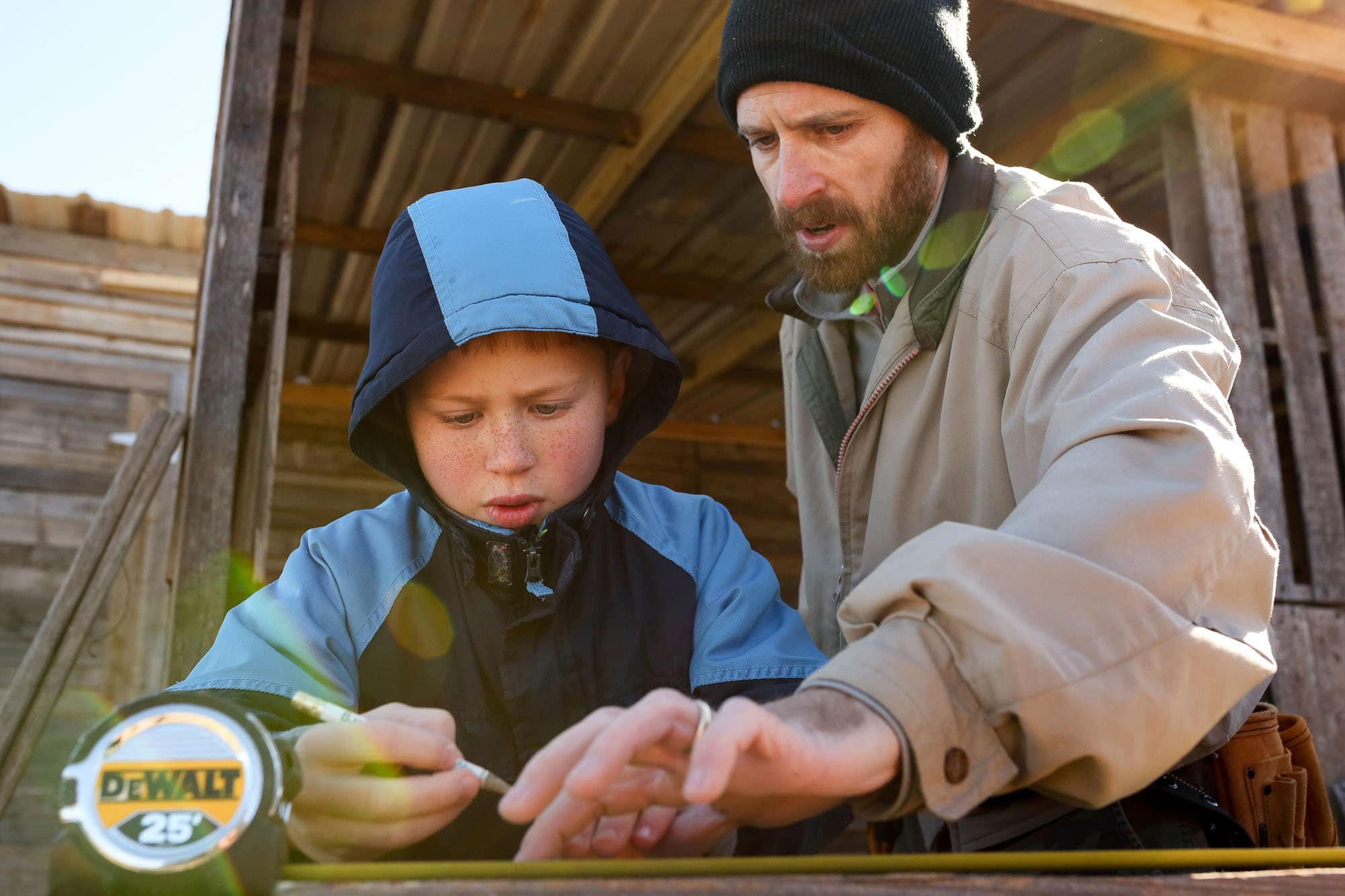 father and son work on barn
