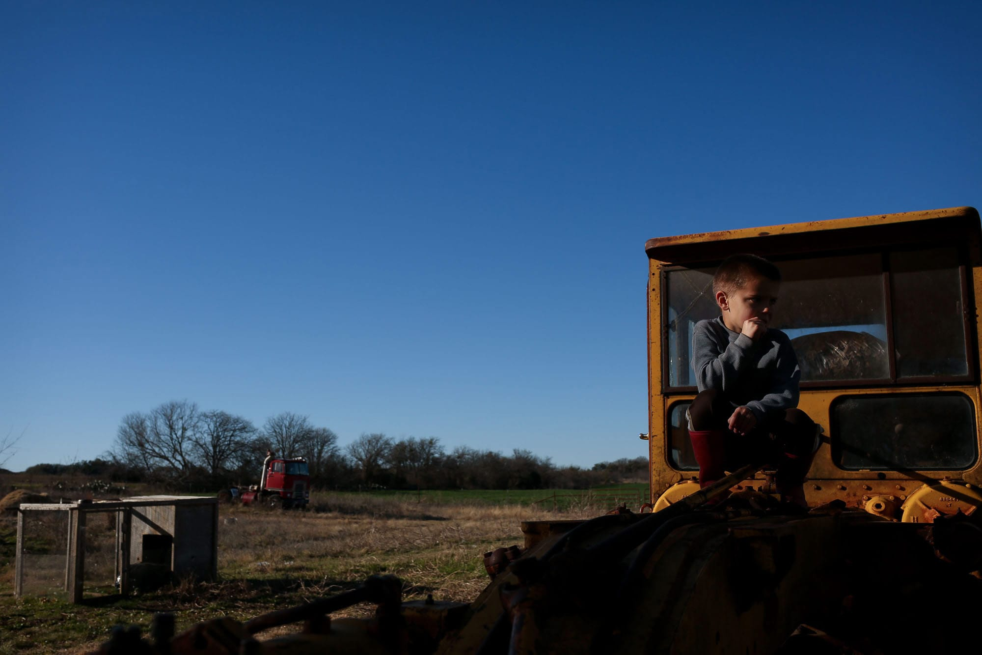 kid sits on old tractor with old truck in background