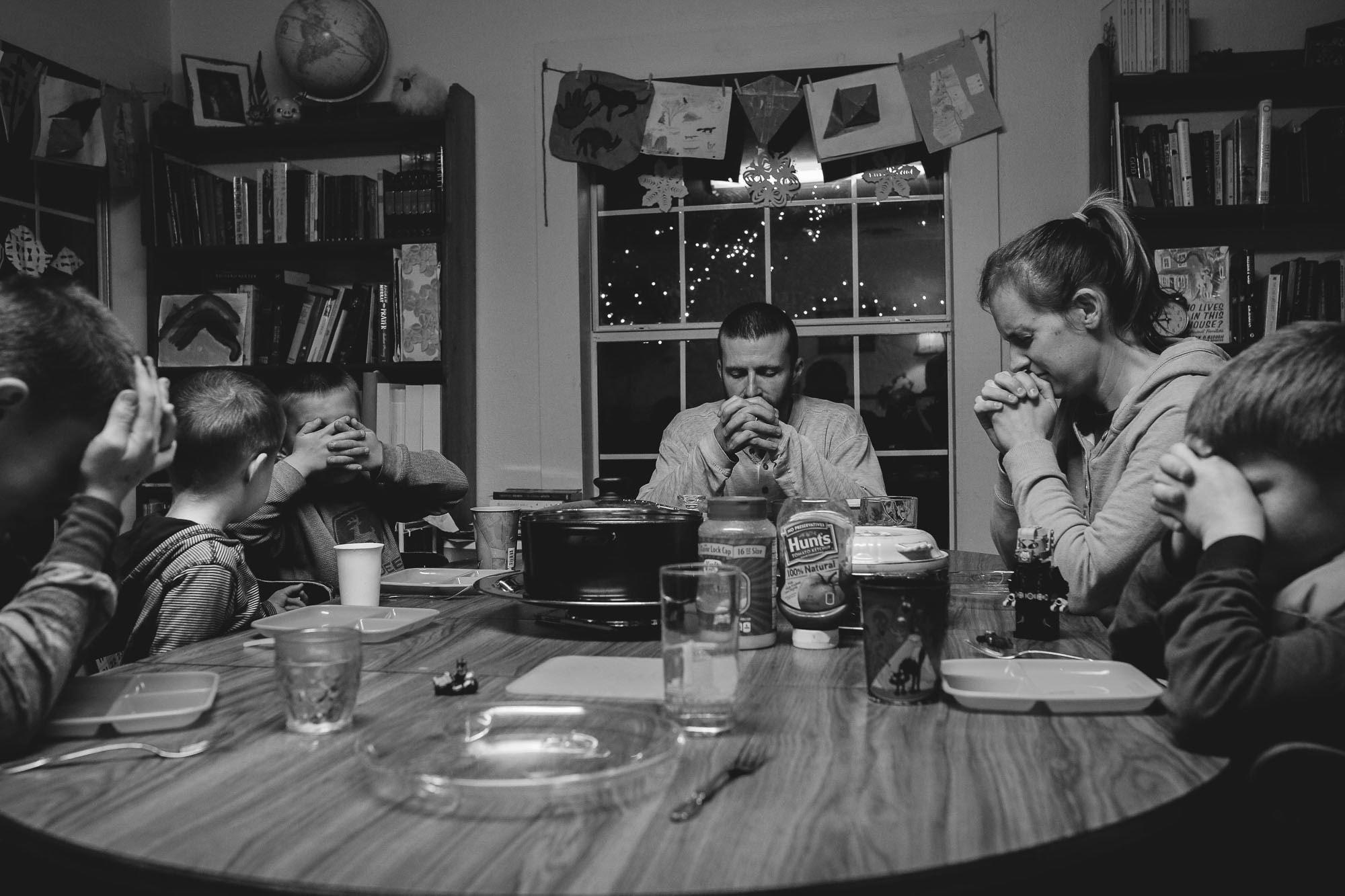 family praying at night before dinner