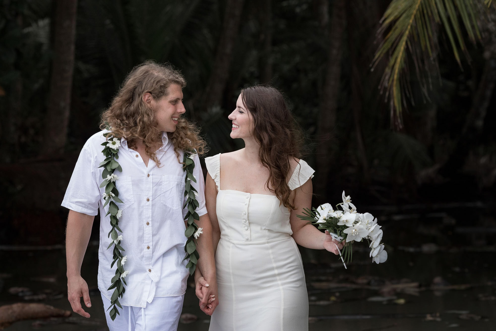 The happy couple strolling after their beach elopement in one of the best places to elope.