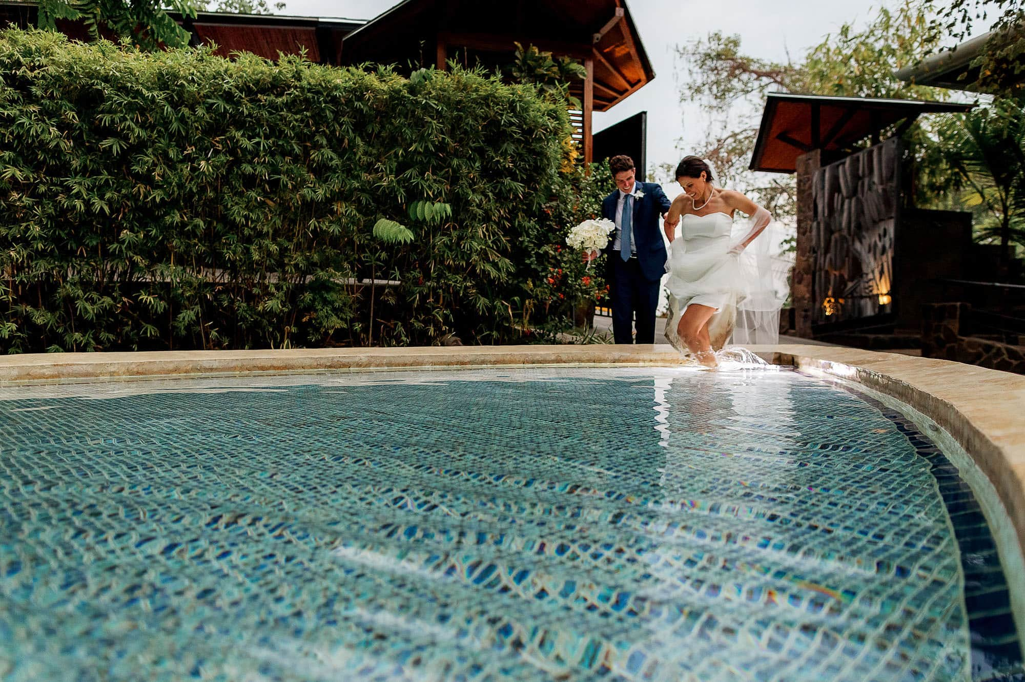 bride splashing in the pool at one of the best places to elope in Costa Rica