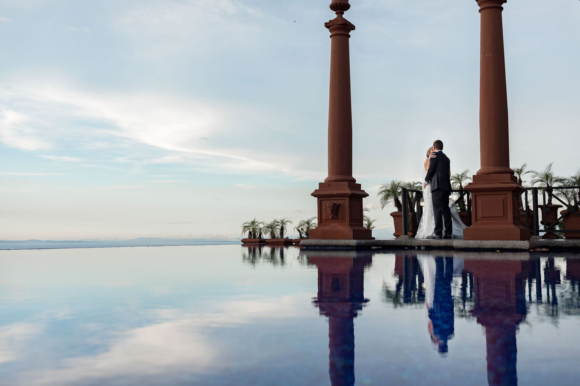 A beautiful moment of just the couple with the infinity pool and the sky