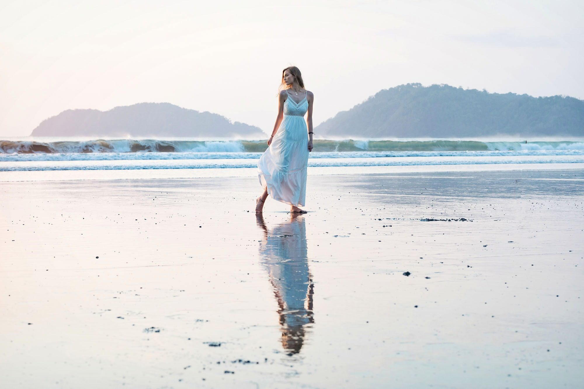 Walking along the beach in a beautiful white dress