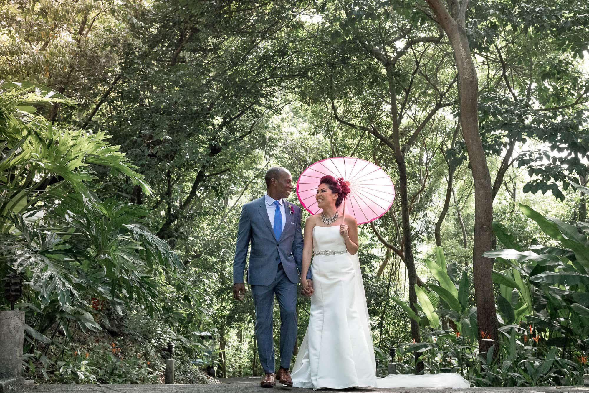 Wedding portrait with delicate pink parasol at Arenas del Mar