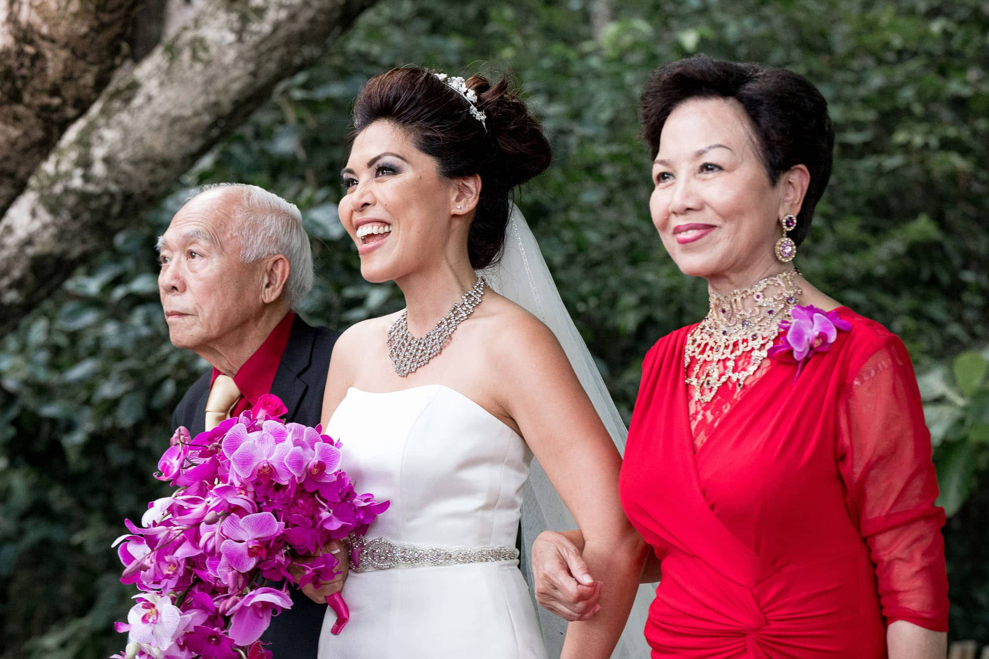 The bride comes down the aisle with her parents at her beachside wedding