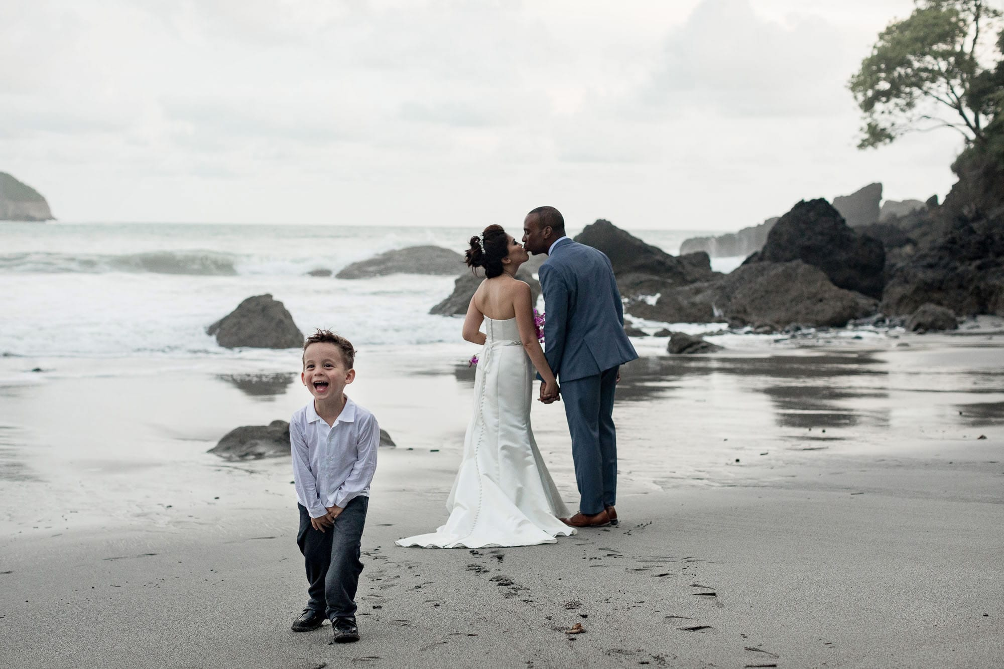 The bride and groom sneak a kiss on the beach and scandalize a little wedding guest!