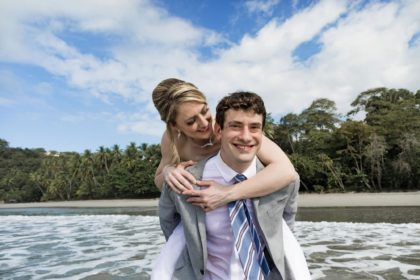 Bride riding piggy back on the groom on the beach after their intimate wedding ceremony.