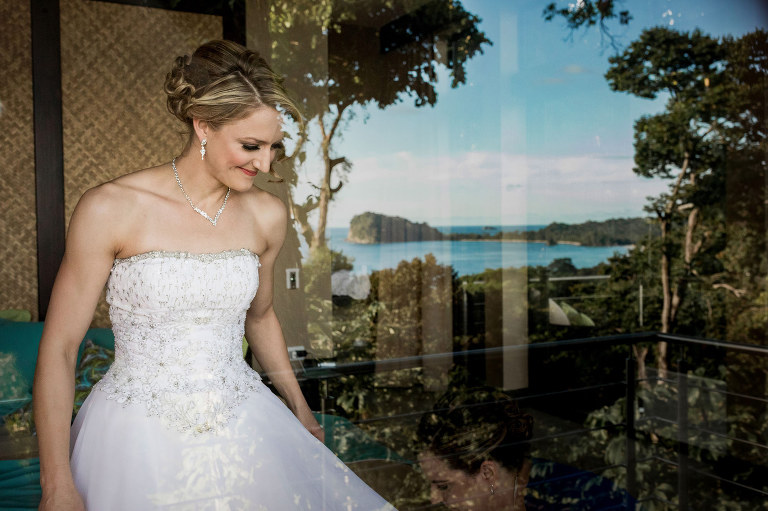 The bride through a glass window at the villa