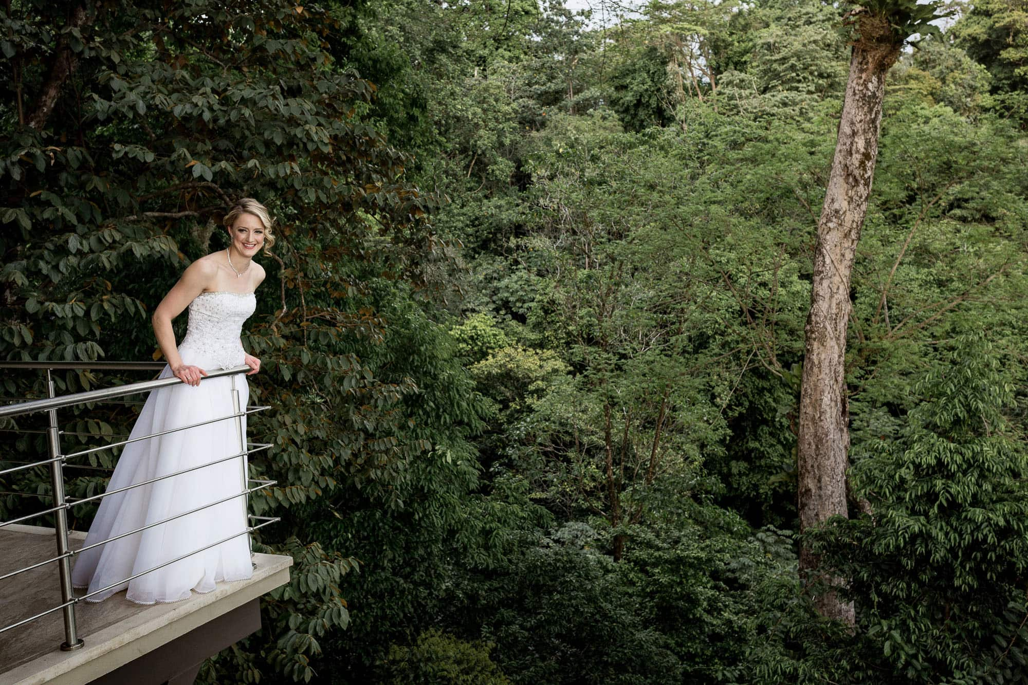 The bride on a balcony with a forest background