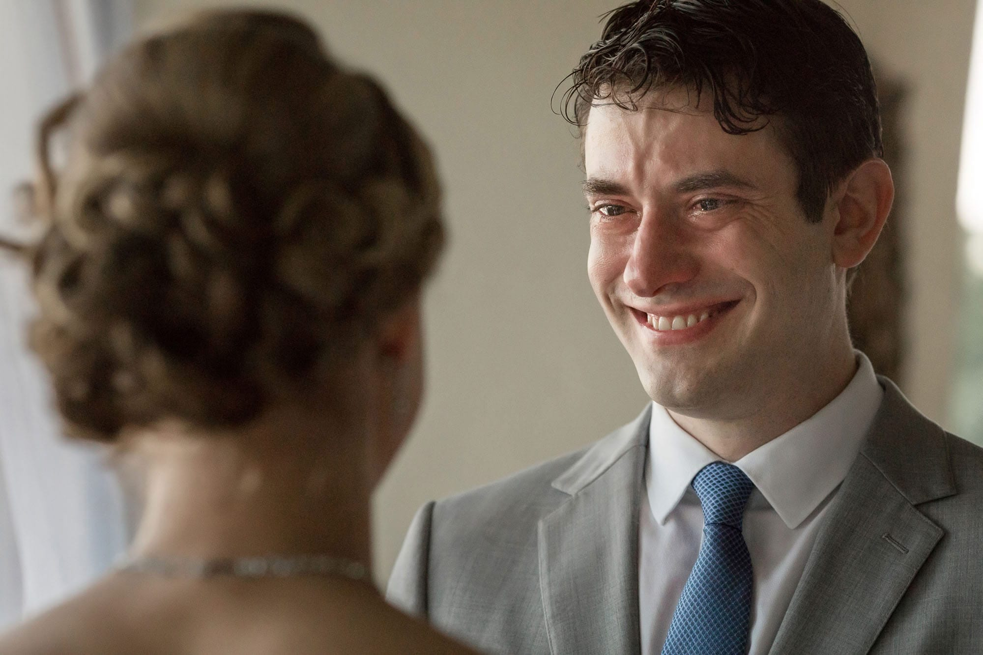The groom smiles with tears in his eyes at his lovely bride.