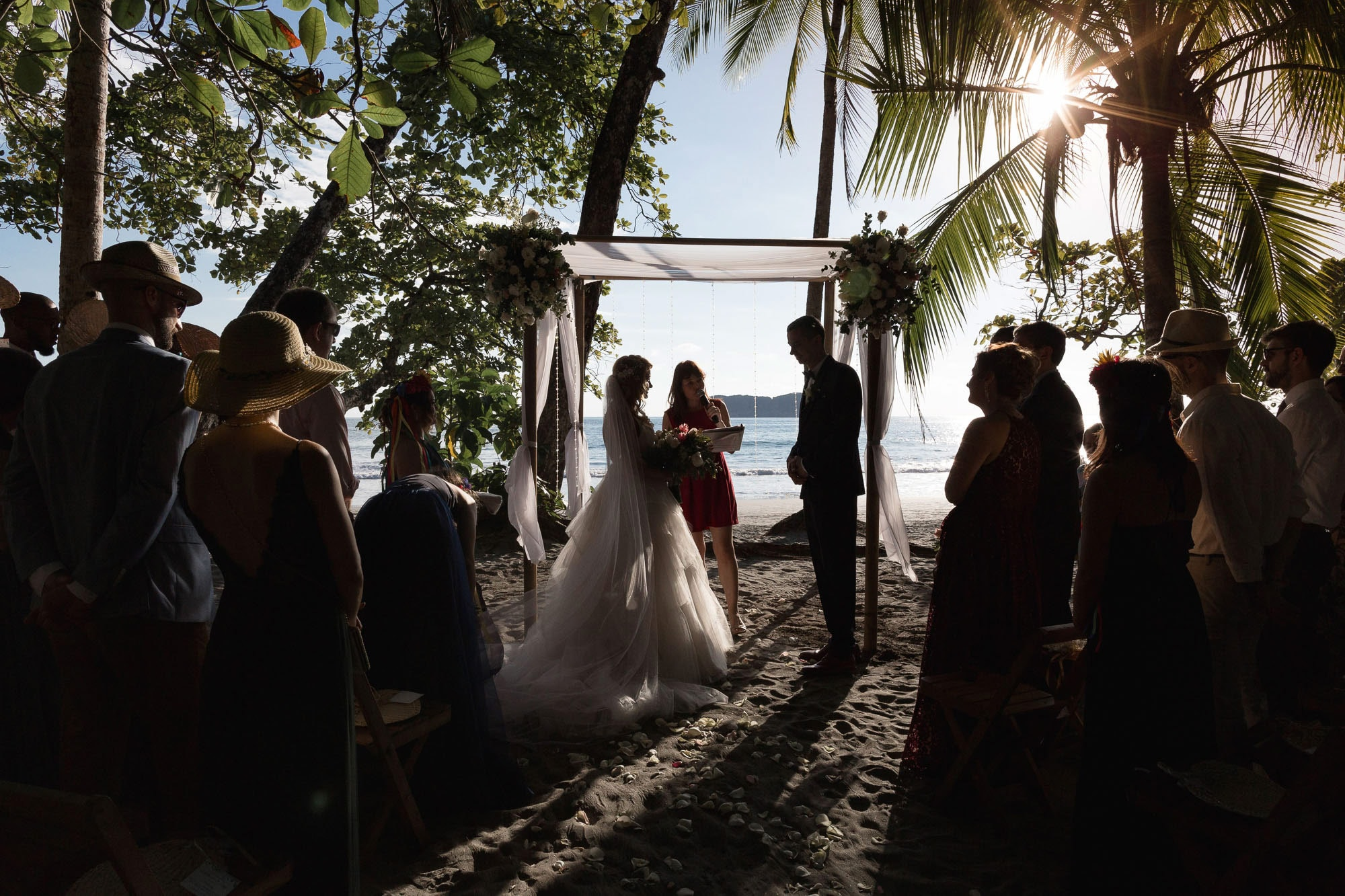 The ceremony setting: the beach, the ocean, and the sunset in the background.