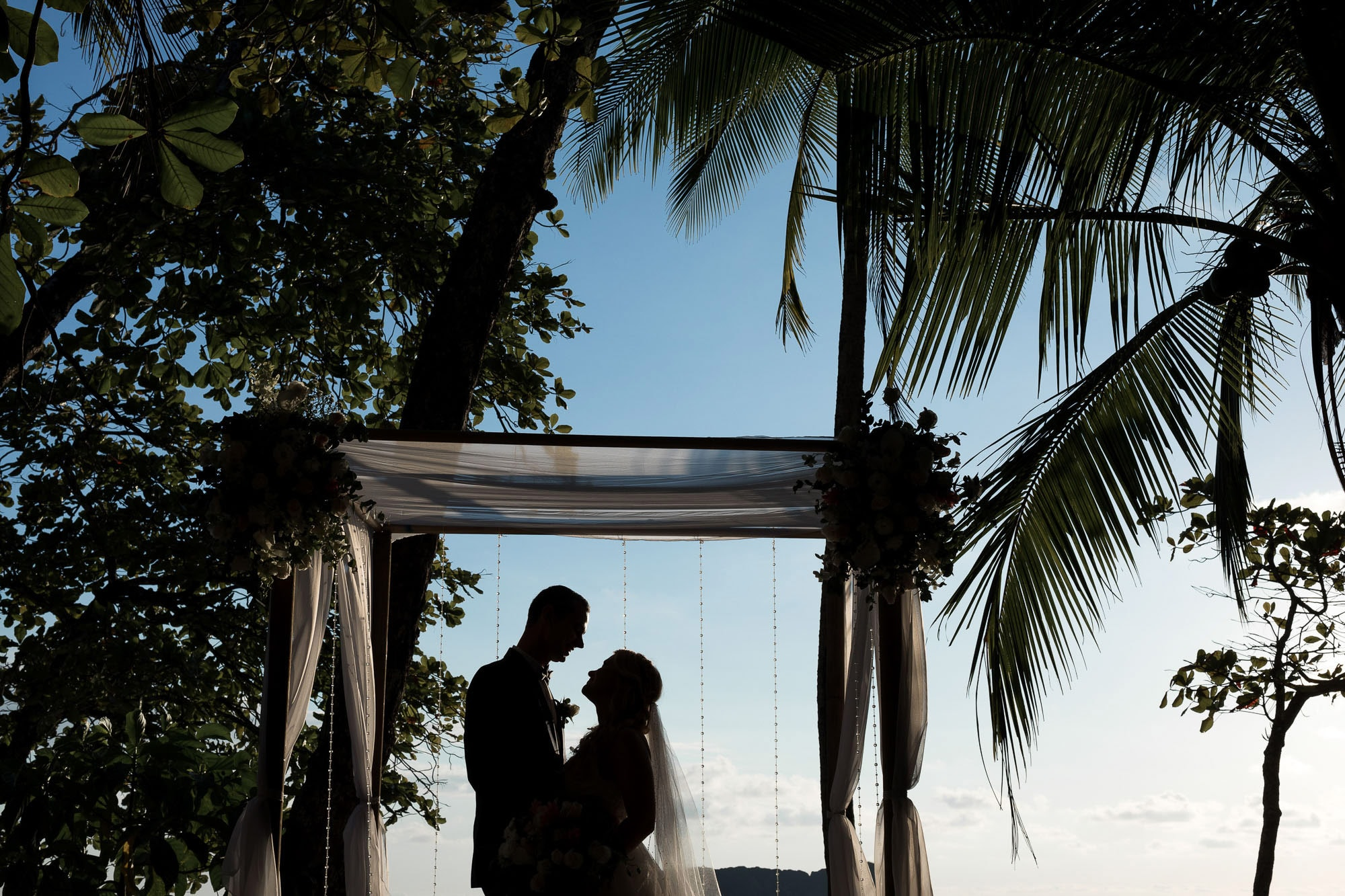 The bride and groom's silhouette perfectly placed in the middle of their wedding arbor.