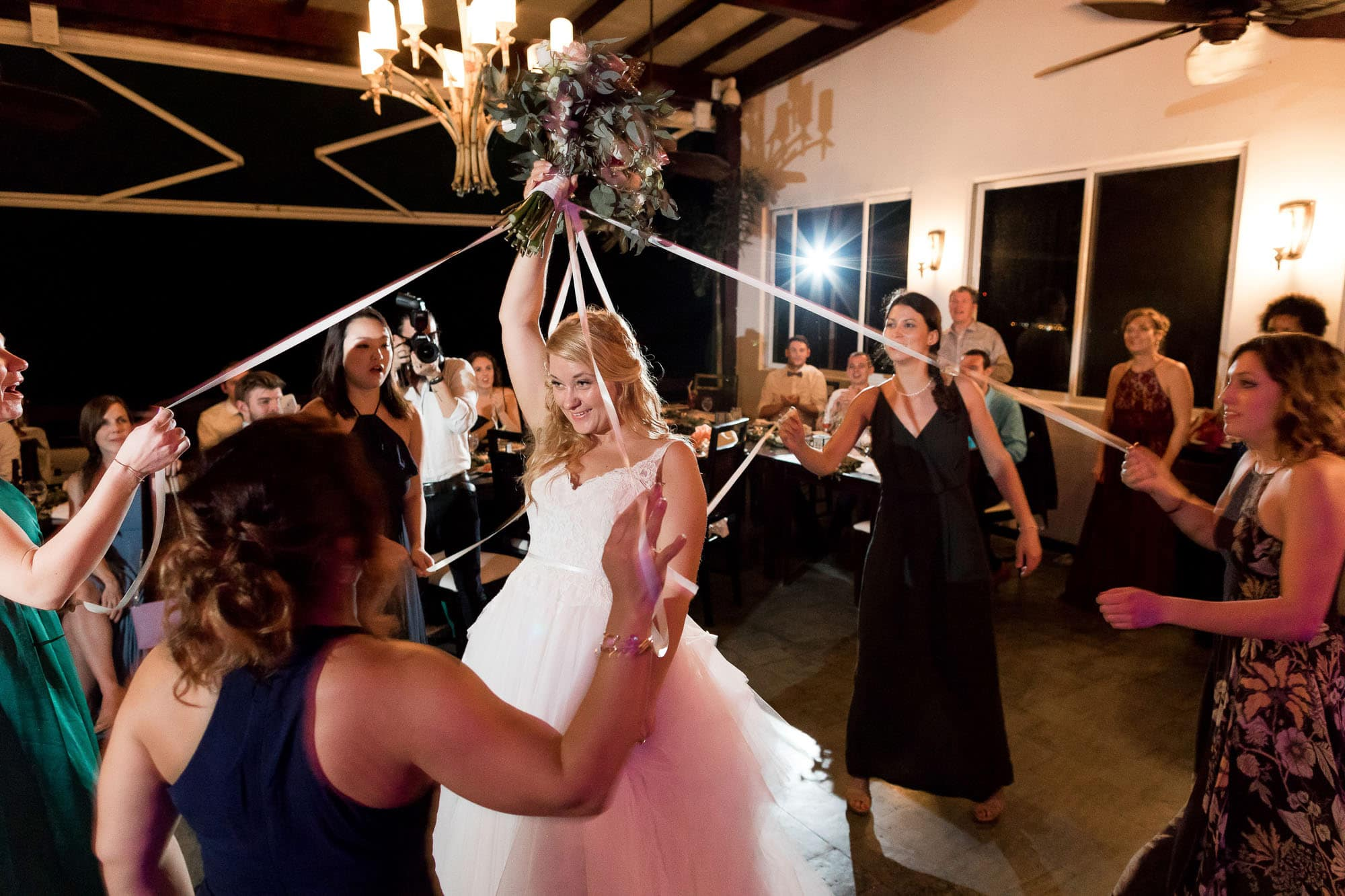 The bride holds aloft her bouquet and the single ladies each grab a streamer connected to it.
