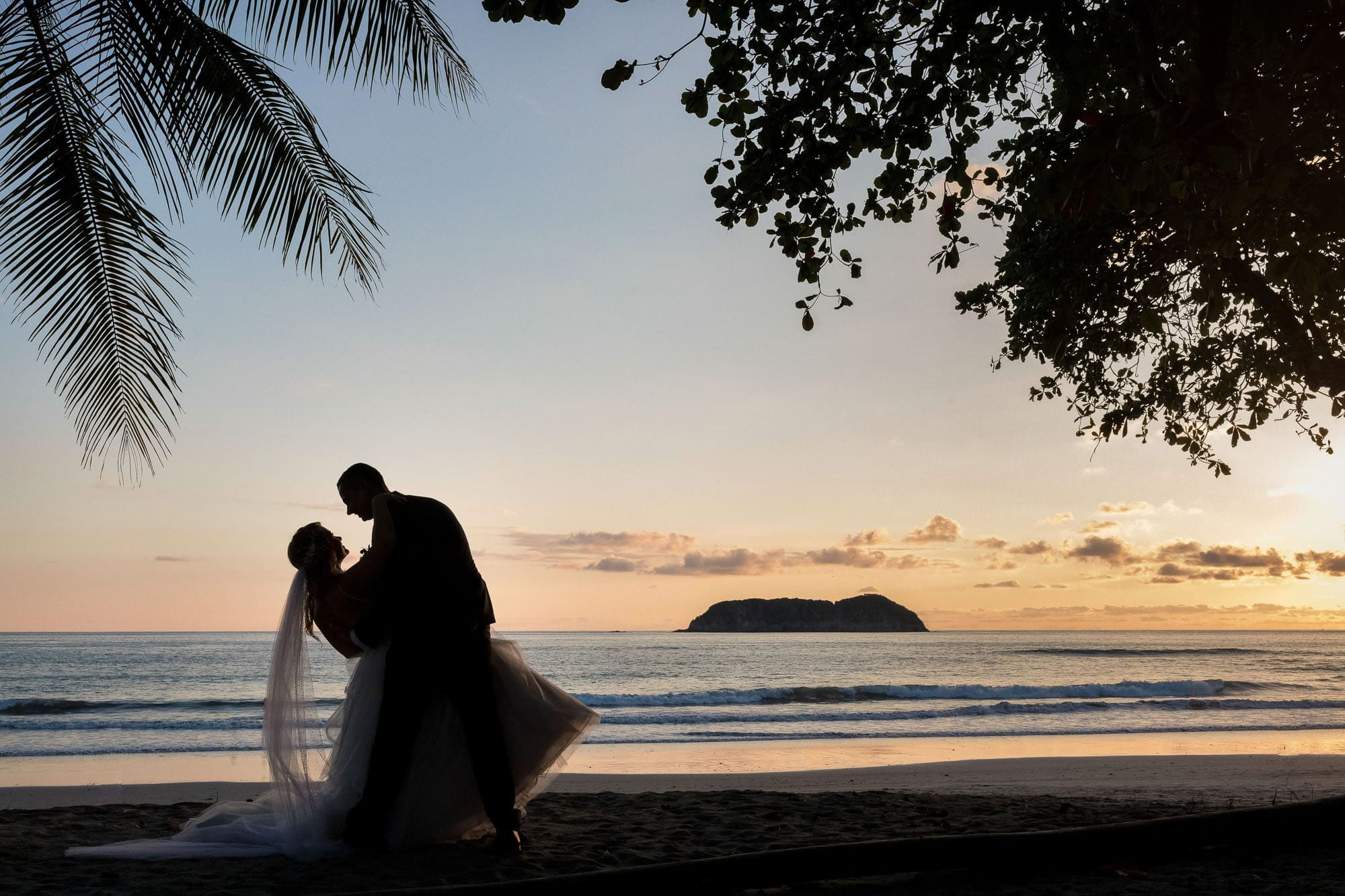 Stunning silhouette of the bride and the groom on the beach in front of an epic sunset.